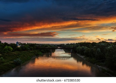 Sunset landscape over a river with beautiful colourful clouds in background