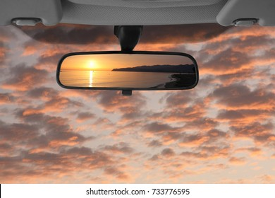 Sunset landscape reflected in the car rear view mirror