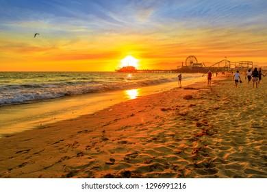 Sunset landscape of Santa Monica Pier reflected on the beach shore. Santa Monica Historic Landmark, Pacific Ocean, California, USA. Amusement park with ferris wheel and roller coaster in summer season