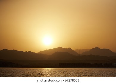 Sunset landscape - sea, mountains, yellow sky