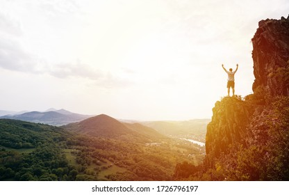 Sunset landscape with silhouette of a standing sporty man and raised-up arms on the top of mountain. High rocks. Looking forwards, success, competition and leader concept.