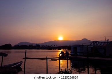 Sunset landscape with still river and distant mountains. Two men watch sunset skyscape. Urban bridge and bay with old ship. Orange skyscape with urban landscape. Cambodia travel photo
