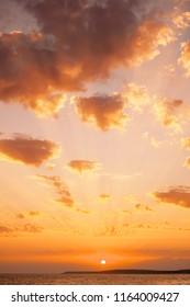 Sunset landscape. Sundown over coastline and sea, beautiful sky with cumulus clouds.