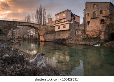 Sunset landscape in Trillo from the river bank with a bridge crossing the river and som houses in the opposite bank, Guadalajara, Spain