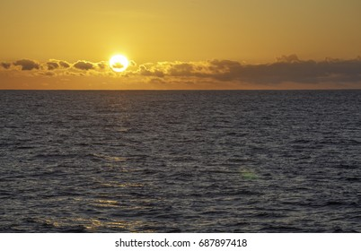 Sunset with large sun over Water at Sea, Pacific ocean