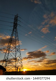 Sunset with a large tower and very long cables with a yellowing sky - image