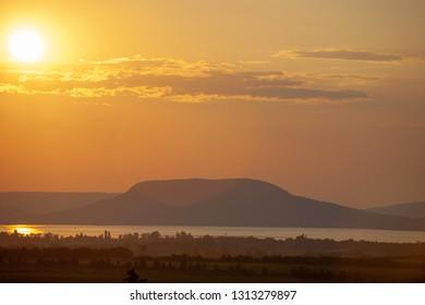 Sunset with lens flare over Lake Balaton and Badacsony mountain in Hungary