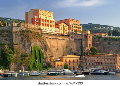Sunset light illuminates historical buildings above the harbor of Sorrento, Southern Italy
