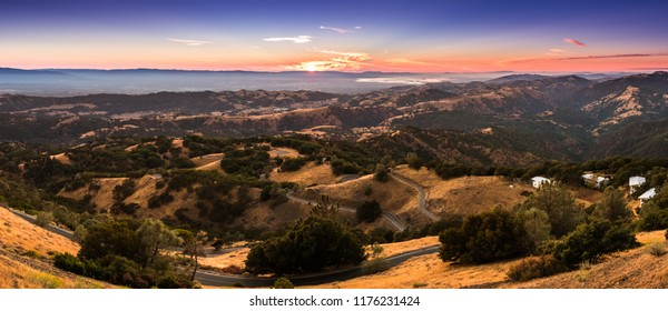 Sunset light illuminating the mountains located in south San Francisco bay area; winding road descending through rolling hills in the foreground; San Jose, south San Francisco bay area, California