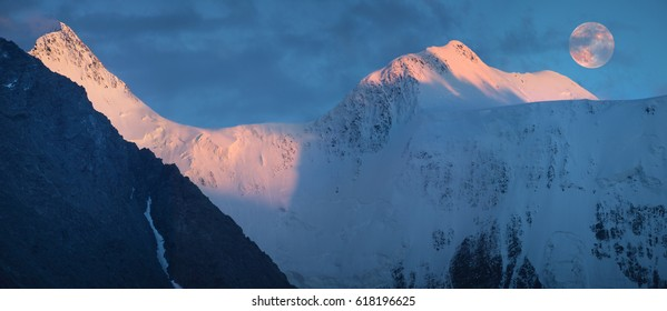 Sunset light in the mountains, full moon over the peaks. Panorama landscape, Belukha Mountain, Altai.