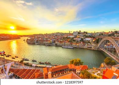 Sunset light on Douro River. Vila Nova de Gaia in Oporto, Portugal. Dom Luis I bridge on background.