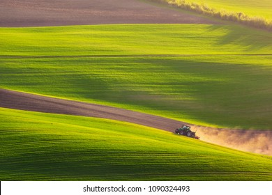 Sunset light over plowing tractor in the spring, South Moravia, Czech Republic