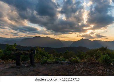 Sunset and light rays behind clouds over peaks and mountains viewed from Mon Phunsuda scenic viewpoint and campsite in Mae Moei National Park, Tak province, Thailand. (words mean Mon Phunsuda)