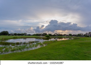 Sunset light shining through the clouds over a grassy field and pond