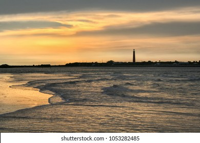 sunset with lighthouse and ocean surf