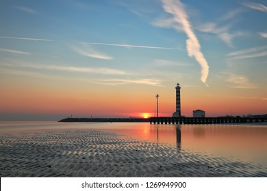 Sunset at the lighthouse on the beach,  with the reflection in the low tide, Jesolo, Veneto, Italy
