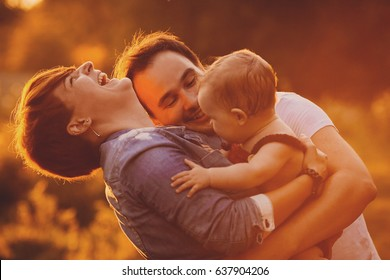Sunset lights shine over kissing parents and their little daughter