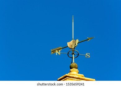 Sunset lit weather vane on clear blue sky