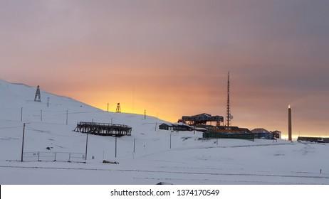 Sunset Longyearbyen from citycenter towards old main conveyer station. Burning sky behind the hill in Longyearbyen on Spitzbergen, Svalbard.