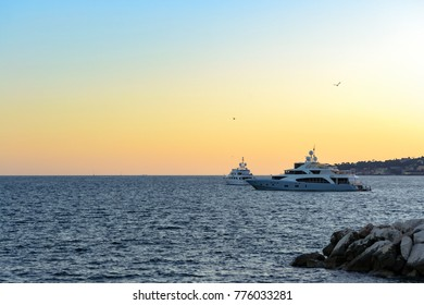 Sunset of a lovely day in the bay of Naples, Italy. Some yachts navigate quietly on the calm water in a minimal romantic view