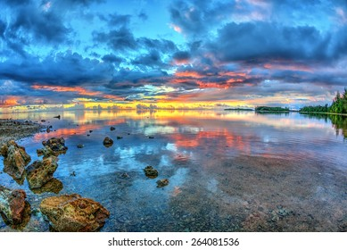 Sunset at low tide with still waters and the rocky coastline of Guam