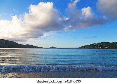 Sunset at Magens Bay beach on St Thomas Island. Rolling wave and horizon over the water at sunset.