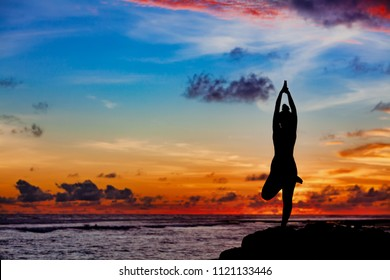 Sunset meditation silhouette. Active woman stand in yoga pose on beach rock to keep fit and health. Healthy lifestyle, fitness training, sport activity on summer family holiday.