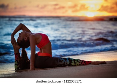 Sunset meditation. Young active woman stretching in yoga pose on sea beach to keep fit and health. Healthy lifestyle, flexibility training, sport activity in sport camp on summer family holiday.