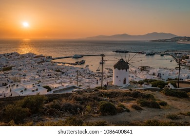 Sunset Mikonos from the hill with old historical windmill and harbor, Mykonos Greece