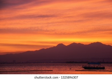 Sunset Mindanao Philippines, With Mount Apo and Banca outrigger boat.