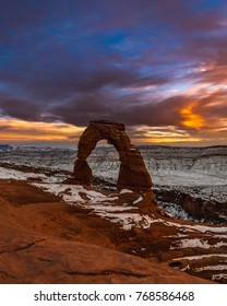 Sunset in Moab, Utah around Delicate Arch during the winter season as snow blankets the area.