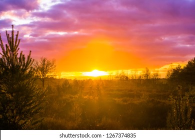 sunset in a moorland landscape with pink nacreous clouds, a rare winter weather phenomenon