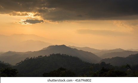 Sunset at the mountain landscape, the sun behind clouds