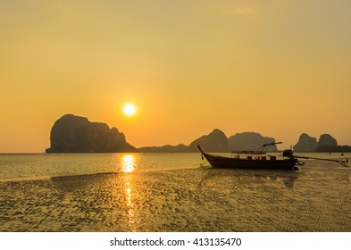 Sunset with mountain and long tail boat on pak meng beach.