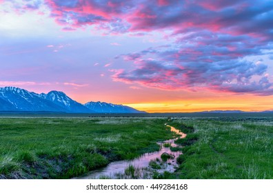 Sunset Mountain Meadow - Colorful spring sunset at a green mountain field with a winding stream near Mormon Row historic district in Grand Teton National Park, Wyoming, USA.