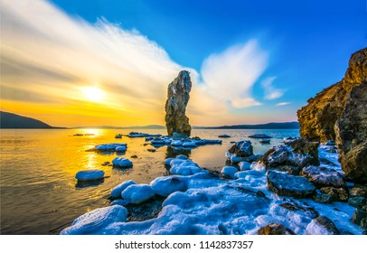 Sunset mountain sea rock snow landscape. Sea rock at snowy mountain sea bay sunset view. Sea rock snow sunset panorama