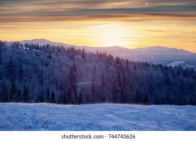 Sunset in mountains, winter landscape. Selective focus on background
