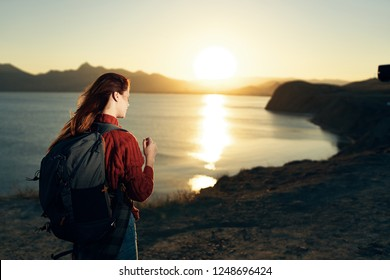 Sunset near the sea and a tourist in the mountains