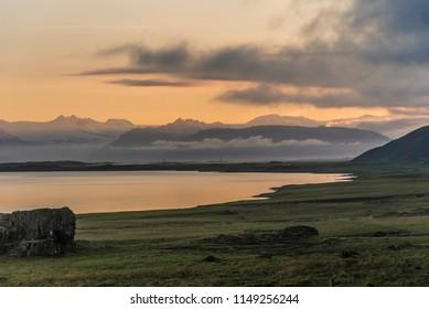 Sunset Near Stokksnes, Iceland with fog, mountains, rocks, and ocean.