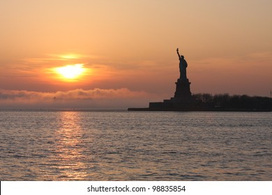 A sunset nearing the Statue of Liberty at dusk.