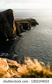Sunset at Neist Point Lighthouse at the coastline of Skye with grass foreground and sunny sky (Isle of Skye, Scotland, United Kingdom, Europe)