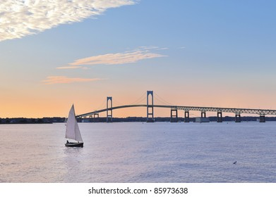 Sunset Newport Bridge sailboats Newport Rhode Island USA. Person in sailboat is in silhouette also changed face and body shape, clothing, hair (person was bald) so they are totally unrecognizable