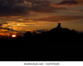 Sunset next to Glastonbury tor, silhouette of tor with a person standing