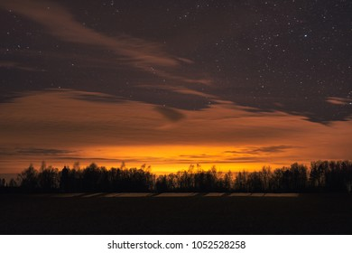 Sunset at night time with clouds and stars in the sky at countryside in Latvia. Electric poles and agricultural land in foreground.