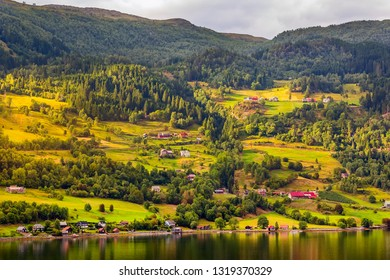 Sunset Norwegian village panorama, green forest mountains and colorful houses, Norway