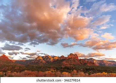 Sunset at Oak Creek Canyon in downtown Sedona, Arizona. In the background geological features, red mesas and buttes, with beautiful blue skies, with white clouds.