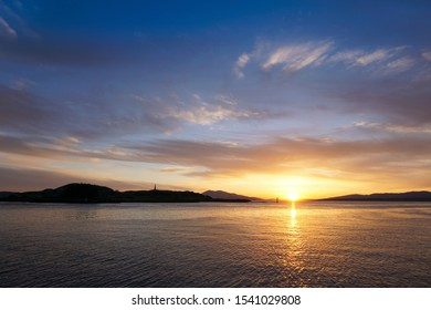 Sunset at Oban Bay and the harbour entrance of Oban. In the background is the island of Kerrera.