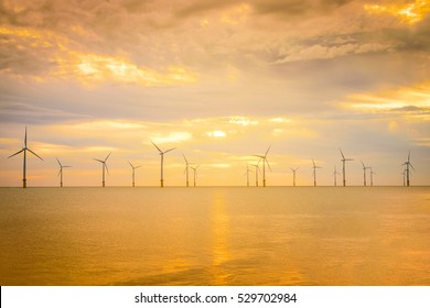 Sunset Offshore Wind Turbine in a Wind farm under construction off coast of England.