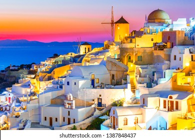 Sunset in Oia, Santorini island, Greece at sunset. Traditional and famous white houses and churches  with blue domes over the Caldera, Aegean sea.
