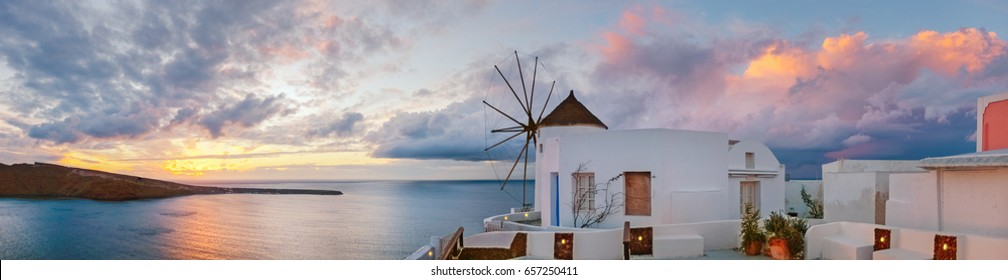 Sunset in Oia village on Santorini island, Greece, panoramic image with traditional windmill